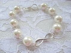 Bracelet +*Eternity,*+ the sign of eternity and white shell pearls. Metal silver colored.