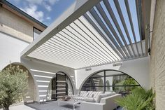 Using tie-rods, side building support and offset supporting posts we can design an Umbris louvre roof that appearance to float above a patio or terrace
