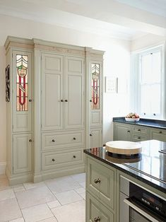 Larder with illuminated stained glass doors and Oak frieze, painted in Farrow & Ball 'Green Ground'. Green Kitchen Cupboards, Kitchen Cabinets Color Combination, Kitchen Cabinet Colors, Kitchen Units, Painting Kitchen Cabinets, Kitchen Paint, Kitchen Walls, Kitchen Ideas, Farrow And Ball Kitchen
