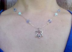 This Star of David necklace is a very classy piece of jewelry. The star is made of silver. On the necklace are Swarovski Beads in colors of blue and transparent with silver bead as well (can make for you with other colors). It is a very gentle Star of David necklace yet very attractive to look at.
