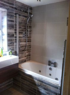 A bathroom feature wall and bath panel of Cimbra Natural wood-effect tiles.