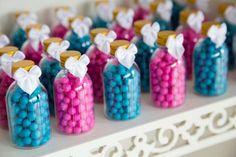 Potinhos com confetes azul e rosa servem tanto para enfeitar a mesa como lembrancinha no chá revelação