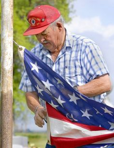 Legionnaire Larry Hyer of Lewiston prepares to raise the flag over the city cemetery. Each year, Hyer places flags on the grave markers of veterans in the Lewiston Cemetery. (Photo by Cody Gochnour)