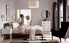Femme dans une chambre à coucher avec lit, fauteuil, miroir, tiroirs et tapis IKEA.