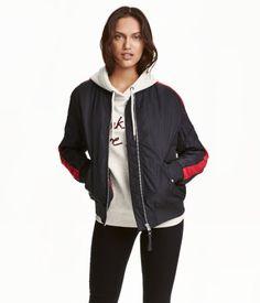 Mørk blå/Rød. En lett vattert jakke i vevd kvalitet med lett glans. Den har liten krage og glidelås foran. Lommer foran med klaff og trykk-knapp. Vrangbord