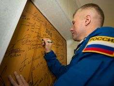 Expedition 33/34 Soyuz Commander Oleg Novitskiy performs the traditional door signing before he and fellow cremates, Flight Engineer Kevin Ford, and Flight Engineer Evgeny Tarelkin depart the Cosmonaut Hotel for their Soyuz launch to the International Space Station, on Tuesday, October 23, 2012, in Baikonur, Kazakhstan. Expedition 33 Crew Hotel Departure (201210230012HQ)