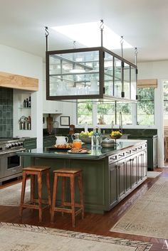 From George and Amal Clooney to Tom Brady and Gisele Bundchen: click for pictures of stunning celebrity kitchens. This beautiful glass cabinet and hunter green storage belongs to Ellen DeGeneres and Portia de Rossi.