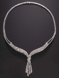 AN ELEGANT DIAMOND NECKLACE Of V-shaped design, suspending at the front a circular and baguette-cut diamond tassel, enhanced by pear-shaped diamond terminals, gathered by a baguette-cut diamond scroll motif, to the circular and baguette-cut diamond three-row surmount, joined by similarly-set scrolled shoulders to the baguette-cut diamond twin-line backchain, mounted in platinum, 17 ins. 20th century or 20th century style, post 1950