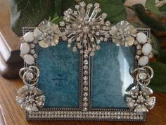 Vintage brooch and earrings mounted on picture frame...good idea for junk store finds!