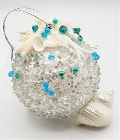 """Beach Christmas ornament w real shells and pretty white coral pieces. This gorgeous nautical coastal ornament is an acetate sparkly ball with pretty white swirls and """"ice"""", and topped with small pieces of real coral and tiny white shells.  Perfect for any beach lover!   I add a crystal and pearl beaded charm dangle of a tiny perfect scallop and a sprinkle of ocean colored beads and sequins to add tons of coastal charm and color. It's one of my favorites this season!! 4"""" acetate ball."""