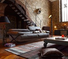 Great vintage industrial space. Leather  light are used to warm this large open space. So many beautiful elements combine here. The wrought iron light stands, warn leather couch, aged steel stairs, exposed brick wall, herringbone wood flooring  pallet coffee table make this look effortlessly cool!