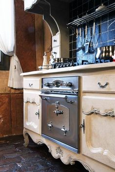 Unique repurposing idea for a kitchen. The stove top and oven have been mounted in a vintage dresser. Gives it a French country flair.
