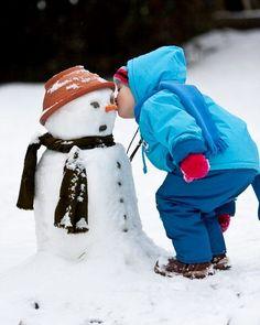 boy kissing snowman at christmas