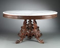 "A lovely American Victorian mahogany center table carved in the Renaissance Revival style retaining its original marble top. Excellent condition.<br><br>Circa 1870<br><br>52"" wide x 35"" deep x 27 1/4"" high"
