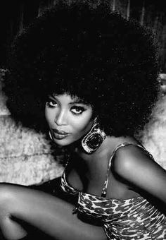Afro hair modelled by naomi campbell. a model getting photographed supporting this hair shows it can be fashionable and may show women with this afro carribean hair to embrace it.