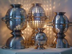 metal pasta strainers stacked to make lights