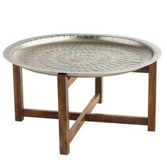 Influenced by Moroccan decor, our coffee table is truly one of a kind. The design on top is hand-etched by artisans so no two are exactly alike. Crafted of aluminum with a matte nickel finish, the top goes splendidly with the bottom frame, which is made of solid mango wood with a warm java finish.