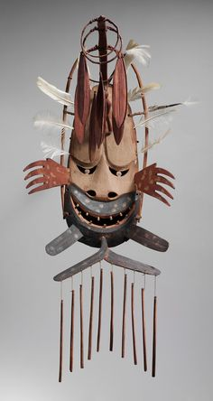 An indigenous Alaskan mask with a ferocious smile decorated with hanging wind…