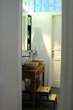 Banheiro com área aberta para acesso aos quartos. Cubas de apoio sobre bancada de madeira. Torneira de parede. Armário sobre bancada revestido com espelho. Tijolo de vidro sobre porta.