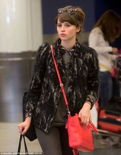 Felicity Jones was seen arriving at LAX wearing the boldly coloured item, with her boyfriend Ed Fornieles in tow.