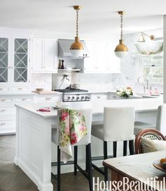White kitchen with brass pendants and slipcovered barstools