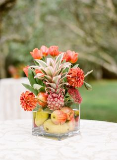 For a tropical wedding, a mixture of fruits and flowers make for a unique center piece.