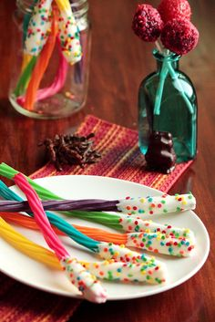 For the acid pops, dip supersour lollipops in honey, and roll them in Pop Rocks for crackling effect. The licorice wands can be made by dipping the tips of colorful licorice sticks in melted white chocolate. Finish them off with rainbow sprinkles.