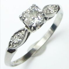 Leafy Shoulders: This charming platinum ring features a twinkling center diamond. On each shoulder, a tiny accent diamond nestles in the center of a graceful leaf shape, a lovely transitional element to the crisp knife edged shank.  Dainty and bright, this classic form is always in style. Ca 1940. Maloys.com