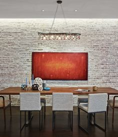 the brick wall adjacent to the custom dining table by brooklyn based uhuru design is
