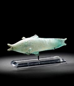 A Roman bluish-green glass fish vessel. Circa 2nd-3rd Century A.D.