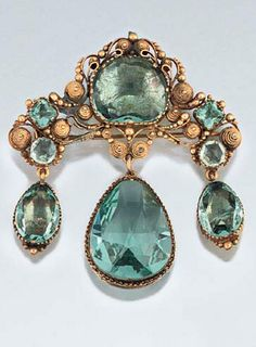 An early 19th century paste brooch  Of girandole design set with 'aquamarine' coloured vari-shaped mixed-cut pastes, the shaped surmount with central cushion-cut single stone and square and circular accents within a cannetille surround, suspending triple pear shaped drops, in gilt metal mounts with coloured foil backs, circa 1830, the central drop in open mount.