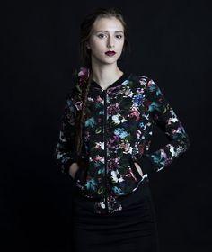 Uhana Design. Mustapohjainen ja monivärinenkukallinen bomber-takki. Edessä vetoketjuja kaksisivutaskua. Suomessa suunniteltu ja valmistettu.