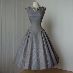 vintage 1950's dress.  Rich slate blue-grey damask with copperish taupe patterning.  Classic silhouette with a a fitted bodice, flattering princess seams, a full gored skirt with pleated side panels.  Fabulous bow design at the double shoulder straps and hips.  Wide boat neckline