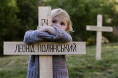 A child embraces one of the 107 wooden crosses, which honor victims of recent protests in Ukraine, in Prague April 23, 2014. Pro-Ukrainian activists set up a symbolical graveyard to pay respect to the 107 people that died during Euromaidan protests. REUTERS/David W Cerny