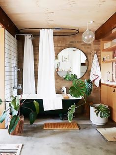 Bathroom with exposed brick, indoor plants, and a freestanding tub