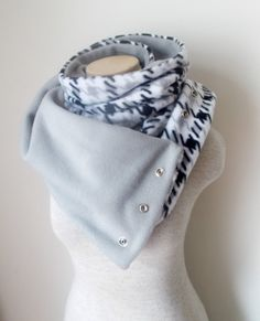 Wrap yourself up in warmth during the crisp and cold fall and winter months with this classic Houndstooth Fleece Scarf. The houndstooth pattern features the colors black, grey, and white. I have lined the inside with a solid grey fleece and attached silver snaps allowing you to wear