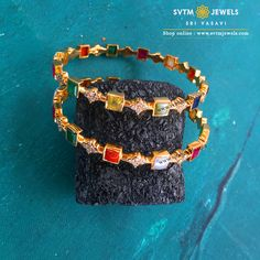 A pair of yellow gold bangle is studded with navaratna stones and round brilliant diamonds. Gold Bangles Design, Gold Earrings Designs, Gold Jhumka Earrings, Antique Jewellery Designs, Gold Jewelry Simple, Emerald Jewelry, Diamond Bangle, Bengal, Diamonds