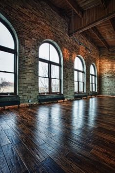 DREAM!! I love everything about this - the exposed brickwork, the darkwood beams, the full length arch windows and the wooden floors. I need this.