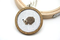 A lovely cross stitched hedgehog in a wooden frame. This pendant hangs from a 60cm silver tone chain. The setting area is 30x30mm and the