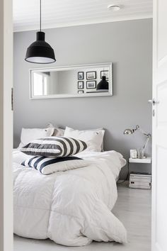 Black & white framed pictures on wall opposite bed