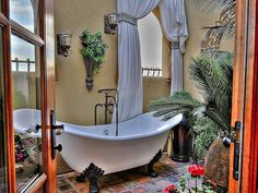 Mediterranean bathing in a beautiful-enclosed courtyard surrounded by lush flowers, plants and a water feature. #bathtub #tub #tropical