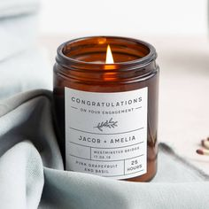 Give a handcrafted engagement gift candle to celebrate an engagement of two special people. Give a handcrafted engagement gift candle to celebrate an engagement of two special people. Designed with a brown apothecary style jar, the candle is hand poured inside and is made from your choice of scents. On the jar, there is a personalised, textured label which has the couple's names, the location and date of the proposal and a cute heart and floral detail. The chosen scent and the burn time of 25 ho Personalized Engagement Gifts, Personalized Candles, Custom Candles, Candle Labels, Candle Jars, First Fathers Day Gifts, White Gift Boxes, Candle Making, Scented Candles