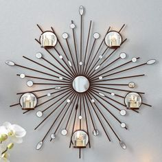 "Starburst Wall Sconce Stellar display for any wall! Mirror glass and acrylic details on rays reflect the beauty of candlelight. Includes five glass votive cups. Hanging hardware not included. 24¾""dia. www.partylite.biz/cndlluvrs"