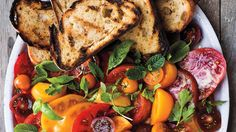 A perfect summer salad of sliced tomatoes is dressed with fresh herbs, salt, and olive oil, and paired with fresh goat cheese and grilled bread.