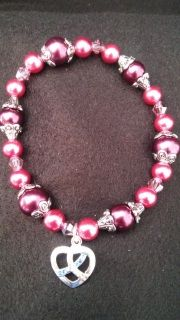 Beautiful two tone rose/mauve 7.5 inch stretch bracelet has a sliver open heart shaped charm with the Down Syndrome awareness ribbon set in blue and yellow rhinestones.