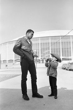 Heavyweight champion Muhammad Ali waits patiently as a young fan, six-year-old Manuel de la Sierra of Mexico City sets his camera for another picture outside Houston's domed stadium, Feb. Mohamed Ali, Muhammad Ali Boxing, Photos Rares, Photo Star, Float Like A Butterfly, Hometown Heroes, Tennis Quotes, Ali Quotes, Sport Icon