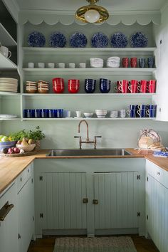 Seafoam green open upper cabinets that display colorful dishes, wood counter top | Studio MRS