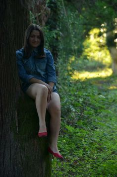 Cute girl sitting on a tree trun in a scenic green summer garden at sunset with sunshine making its path through trees---attractive attire