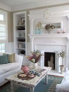 My dream is to have a white fireplace like this one, complete with shelves on either side. I don't like the extra shabby coffee table. I'd paint it white or aqua to match the carpet.