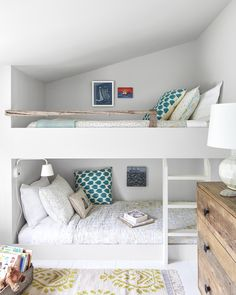 Built-in bunk beds in the daughters' shared room reinforce the home's understated rustic vibe. The simple, streamlined bunks and ladder, for example, balance the reclaimed driftwood railing and dresser made from old barnwood. A citrine dhurrie (serenaandlily.com)